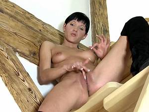 Sandra fingers her pussy on the wooden stairs